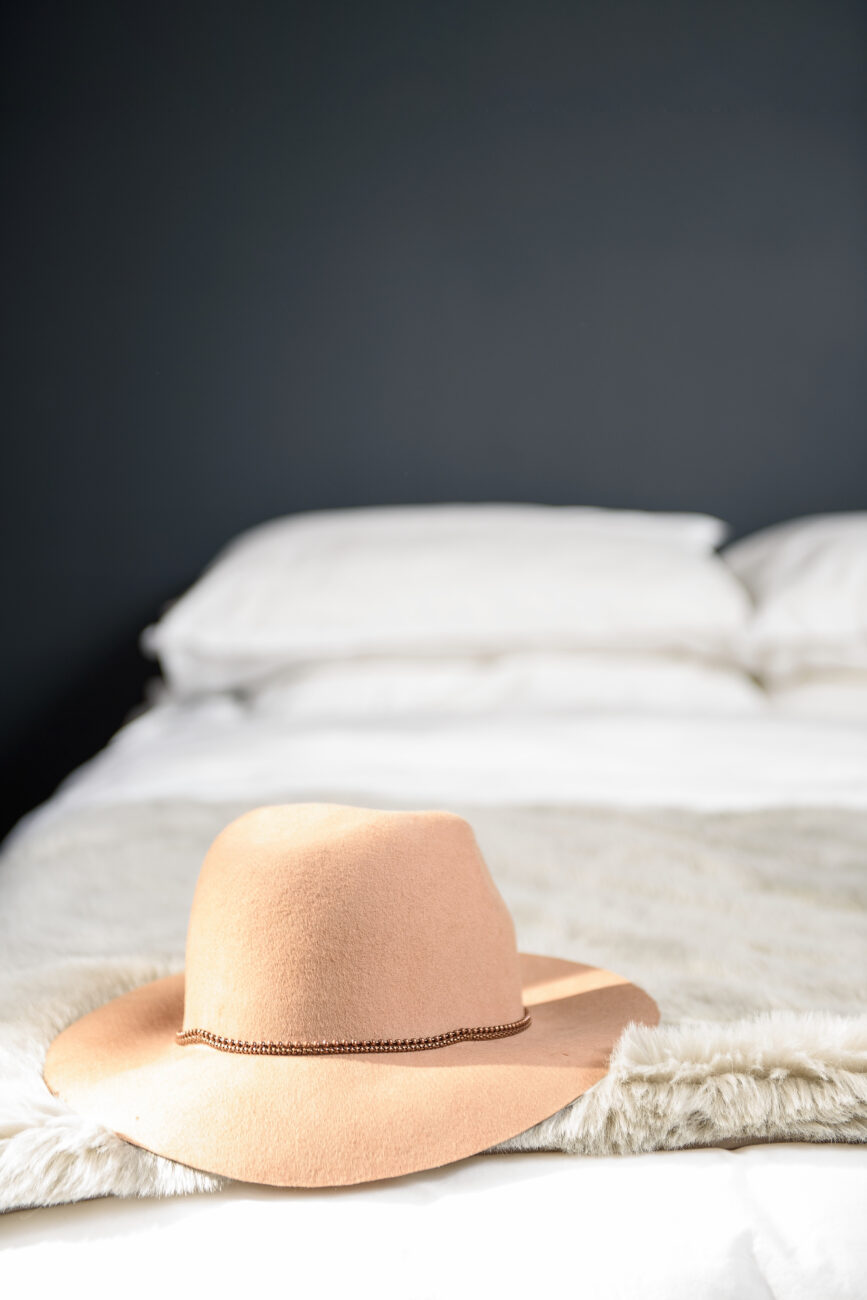 camel hat laying on white bed